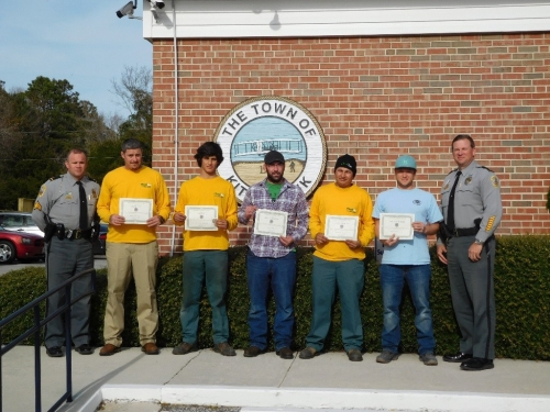 Grounds Guys crew holding awards by the Kitty Hawk Police Department